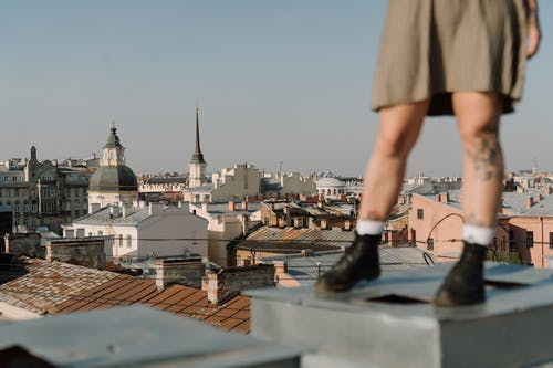 Woman in Brown Skirt and Black Shoes Standing on Top of Building