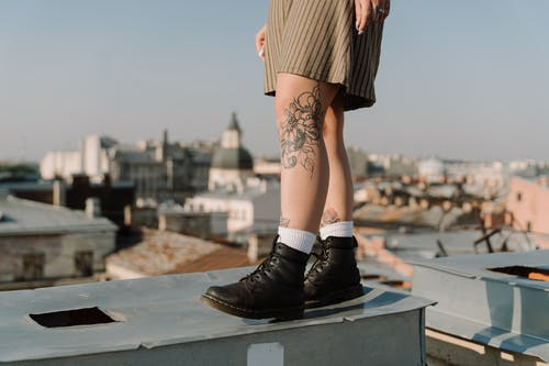 Woman in Black Leather Boots Sitting on Gray Concrete Railings