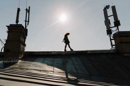 Man in Black Jacket and Pants Standing on Top of Building