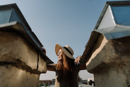 Woman in Brown Long Sleeve Shirt Wearing White Sun Hat Sitting on Brown Concrete Wall during