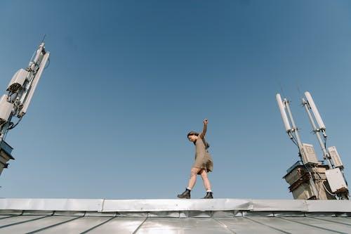 Mężczyzna W Brązowych Szortach Skoki Na Biały Betonowy Budynek