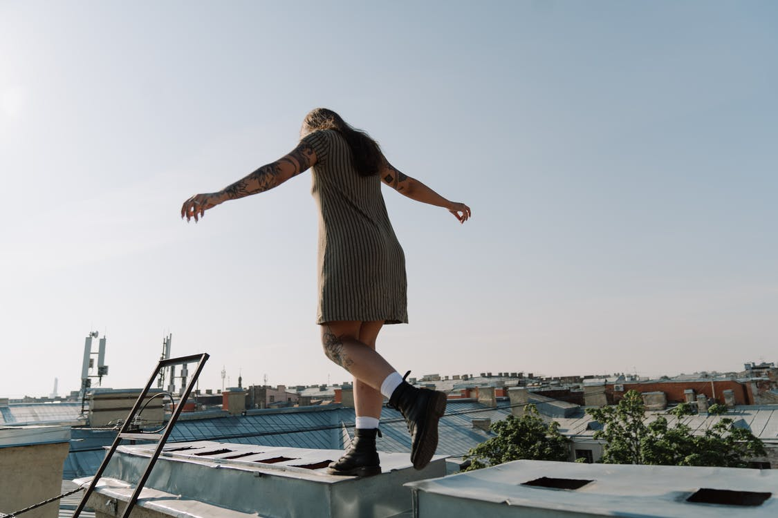 Woman in Brown Dress Standing on Blue Floor