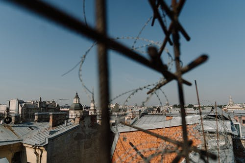 Brown Metal Fence Near White Concrete Building
