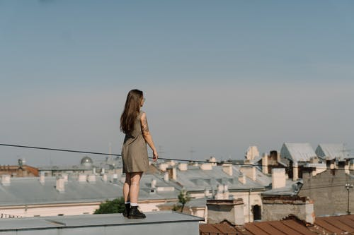 Woman in Brown Sleeveless Dress Standing on White Concrete Building