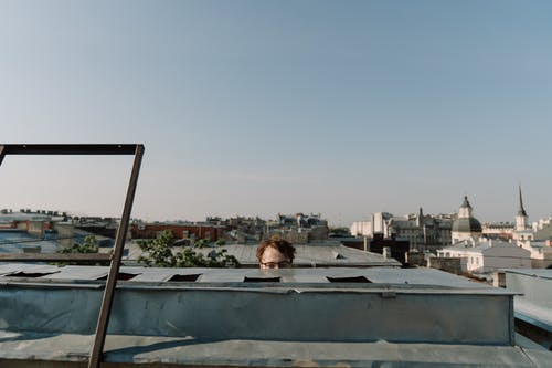 Woman in Black Shirt Sitting on Top of a Building