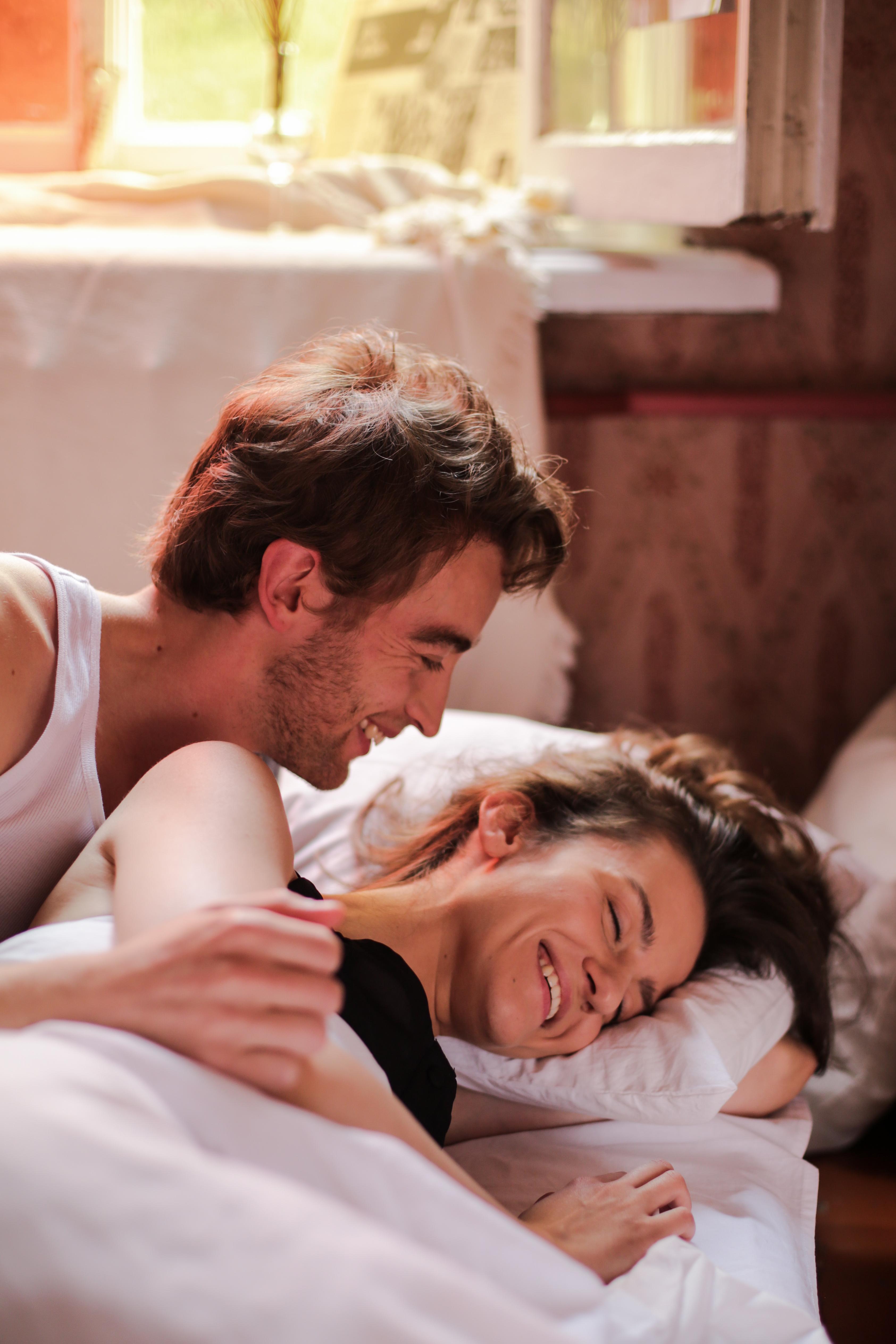 man in white tank top kissing woman in black tank top