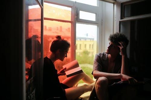 Man in Black Suit Sitting Beside Woman in Black Dress