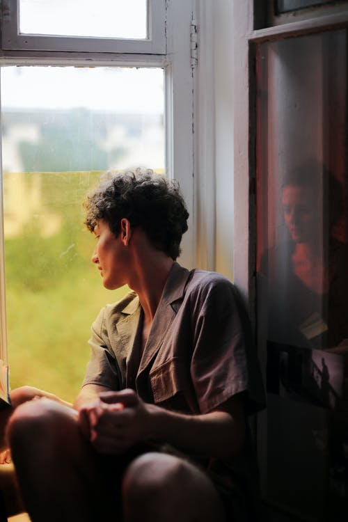 Man in Gray Button Up Shirt Sitting Beside Window
