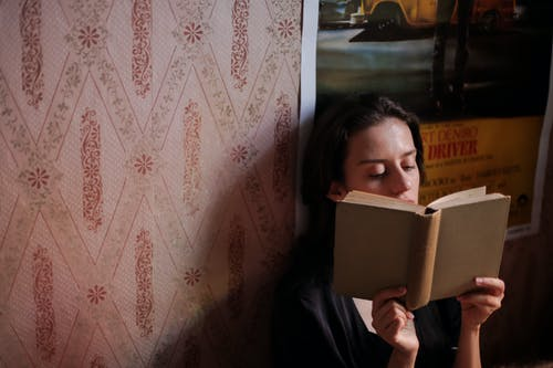 Woman in Black Jacket Holding White Book