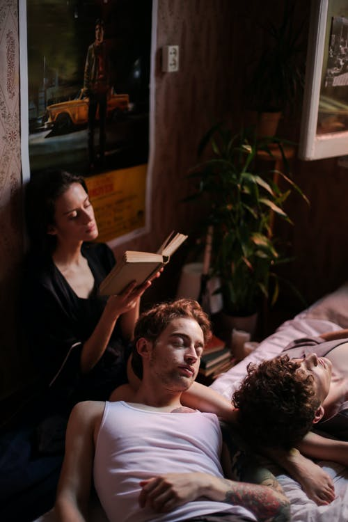 Man in White Tank Top Lying on Bed Beside Woman in Black Shirt