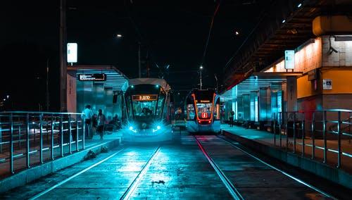 People Standing Near Red Train during Night Time
