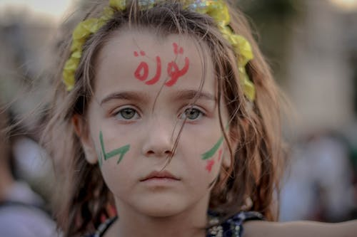 Unemotional little girl with symbols on cheeks and Arabic script on forehead looking at camera on blurred background