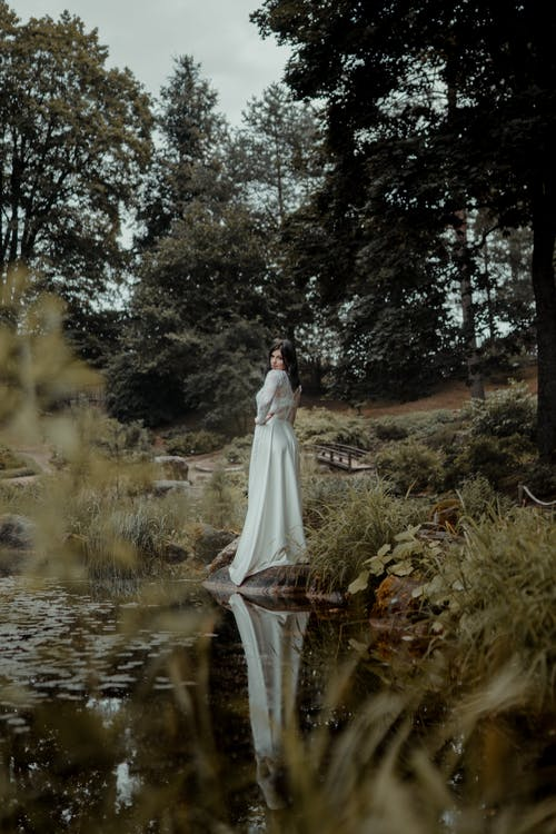Woman in White Wedding Dress Standing Near River