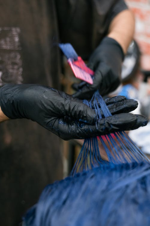 Person in Black Leather Gloves Holding Blue Textile