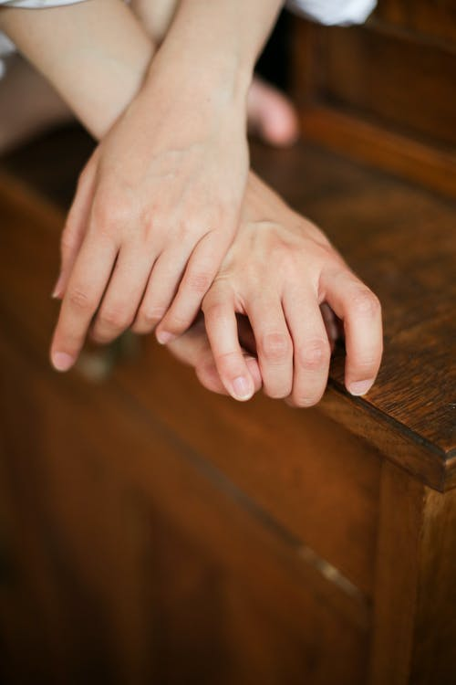 Persons Hand on Brown Wooden Table