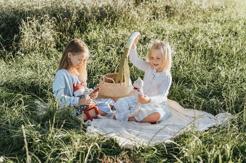 2 Girls Sitting and Playing on a Field