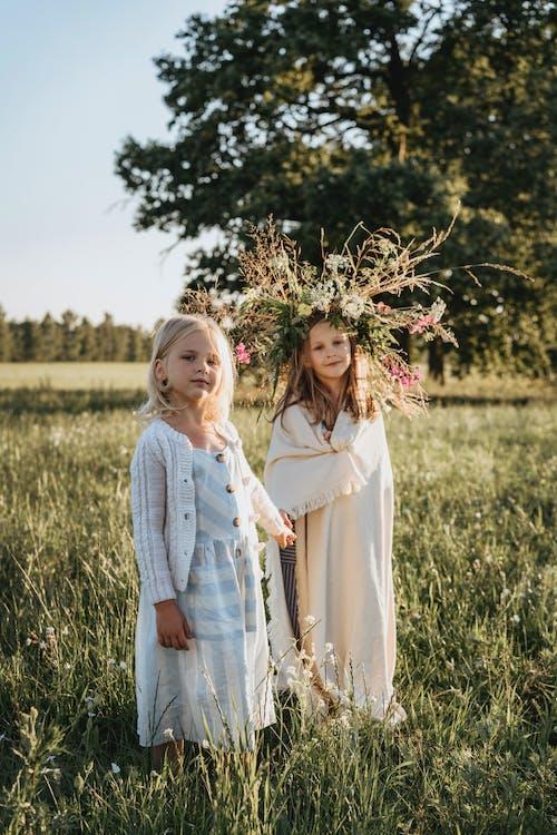 Little Girls Standing on a Grass Field