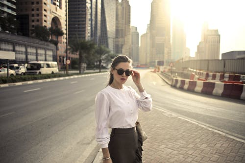 Woman in White Long Sleeve Shirt and Black Skirt Standing on Road