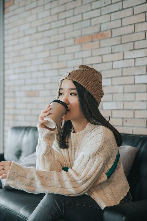 Dreamy Asian woman in stylish wear drinking coffee on sofa