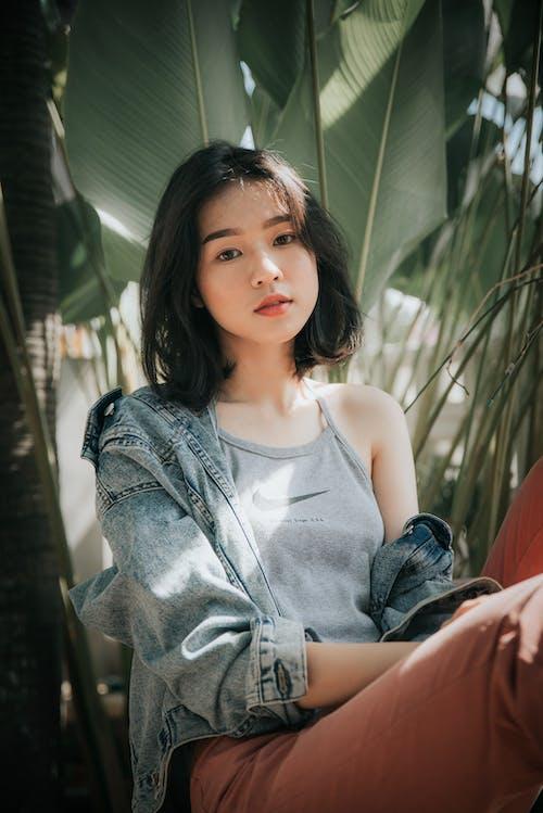 Dreamy Asian woman in trendy wear among plants