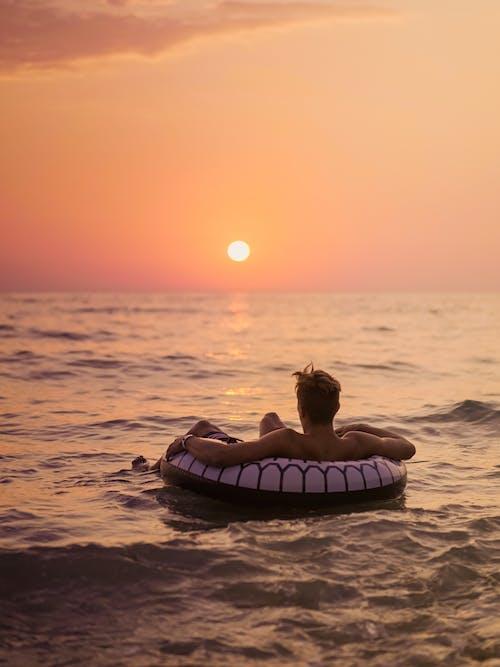 夕日を眺める海の膨脹可能なリングの顔のない男性旅行者