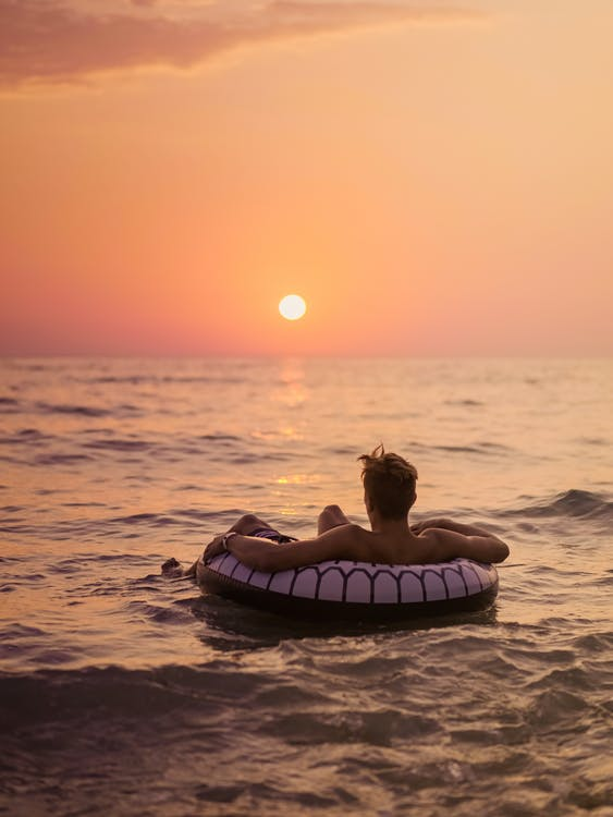 Back view of unrecognizable male tourist lying in inflatable ring on wavy sea while contemplating bright sky with sun in evening