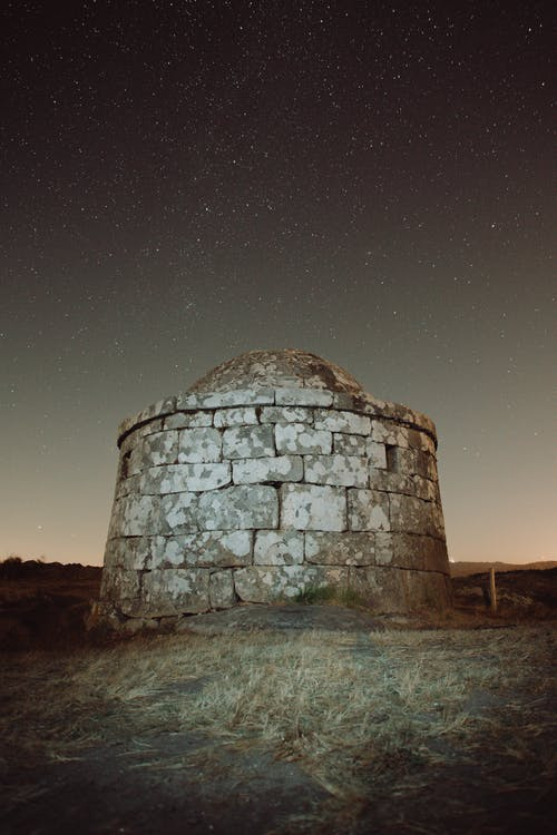 Picturesque scenery of lighthouse with remains of ancient fortress located on grassy ground against starry sky in night time in nature