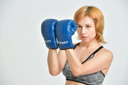 Young confident female in sports top clenching fists in blue boxing gloves on grey background