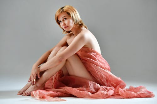Side view of young naked female wrapped in pink drapery sitting on floor looking away