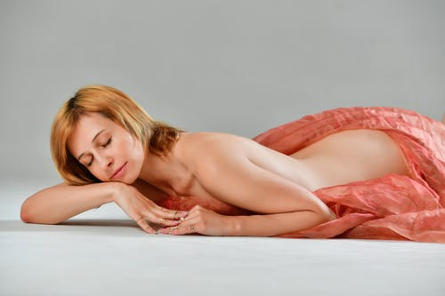 Naked woman covered with pink veil lying on floor