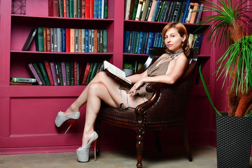 Side view of young female in club short dress and fancy high heels shoes sitting in armchair and reading book in library
