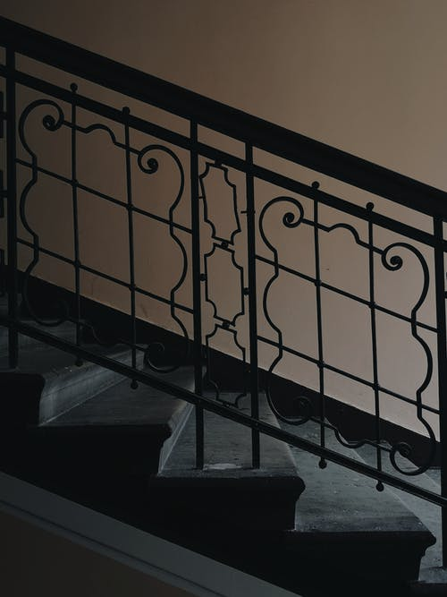 Stone steps with metal handrails and decorative elements creating patterns placed near light wall in corridor inside modern apartment building