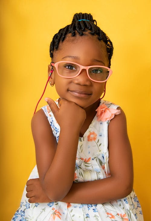 Smiling black girl in glasses touching chin and looking at camera