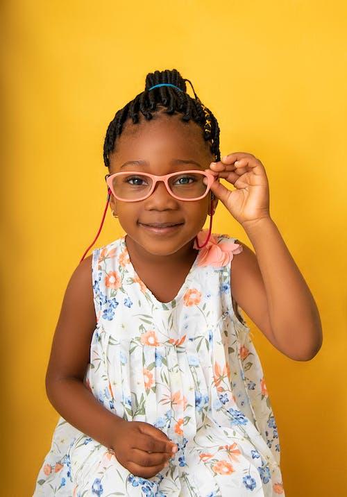 Cheerful black girl adjusting eyeglasses and smiling