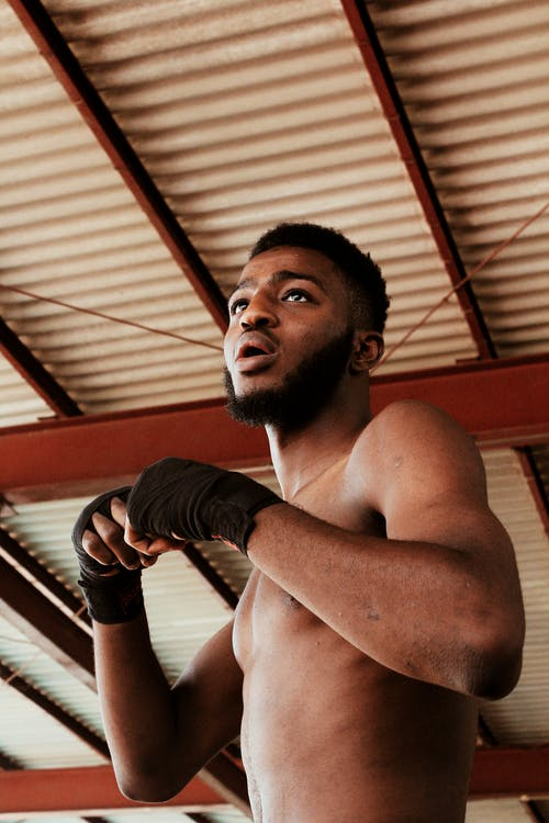Low angle of African American male boxer with opened mouth in bandages looking away while training in spacious room in daytime