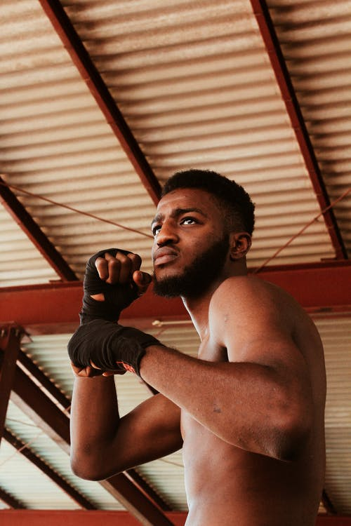 From below of aggressive bearded shirtless African American male fighter with hand near face practicing boxing punches while standing in stance