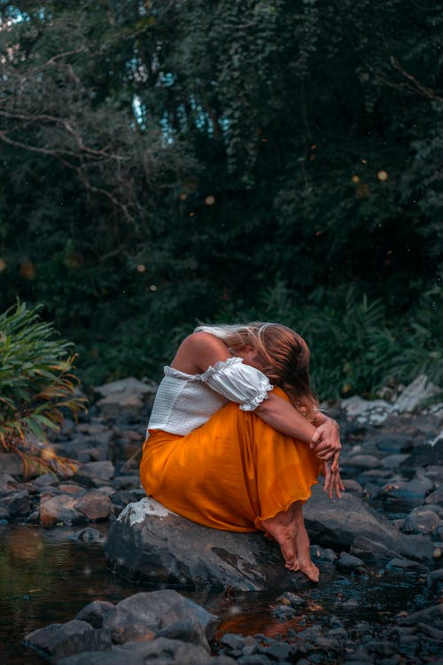 Woman in White Shirt and Orange Skirt Sitting on Rock