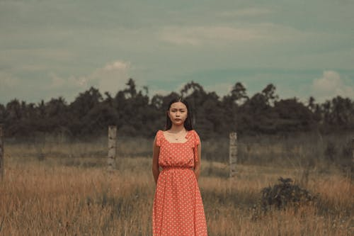 Young ethnic female with hands behind back standing in meadow against trees and looking at camera