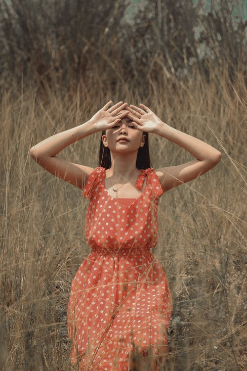 Graceful ethnic woman covering face with hands in dried grass