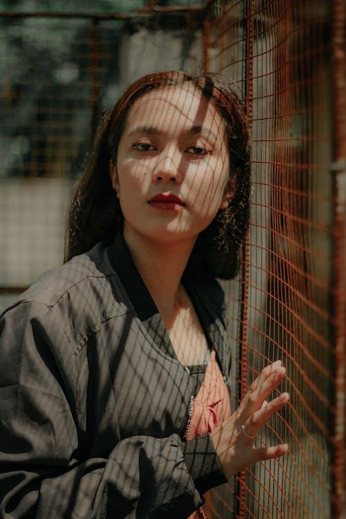 Provocative ethnic woman standing near net