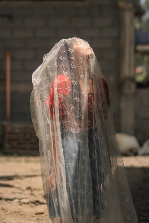 Ethnic girl with closed eyes in dress under thin veil in native town
