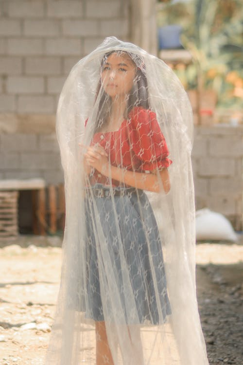 Asian girl in bridal veil standing with clasped hands in village and looking at camera