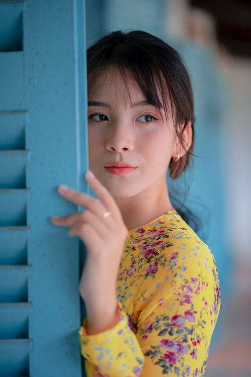 Asian woman standing near open door