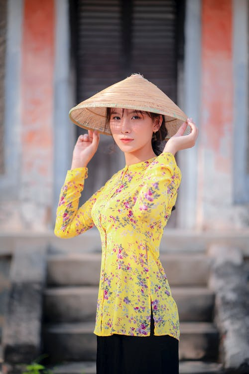 Asian woman in traditional hat near building