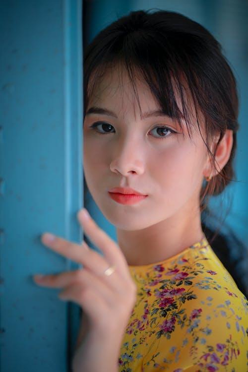 Young Asian woman near blue wall