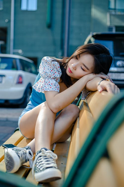 Dreamy Asian woman resting on bench in city