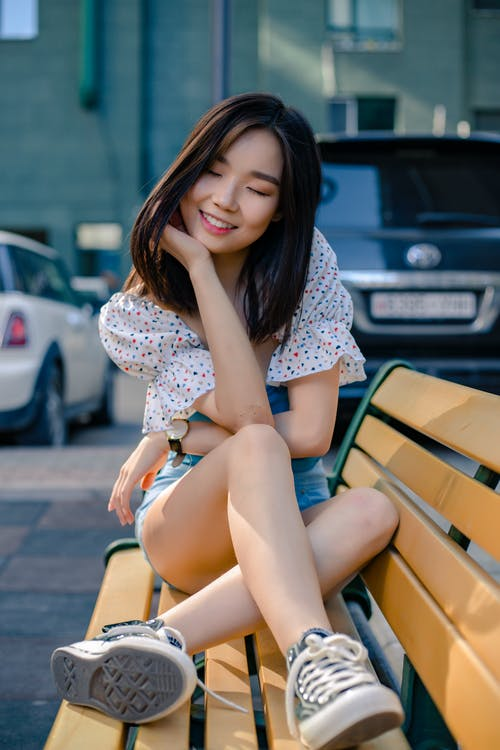 Dreamy Asian woman on street bench in city