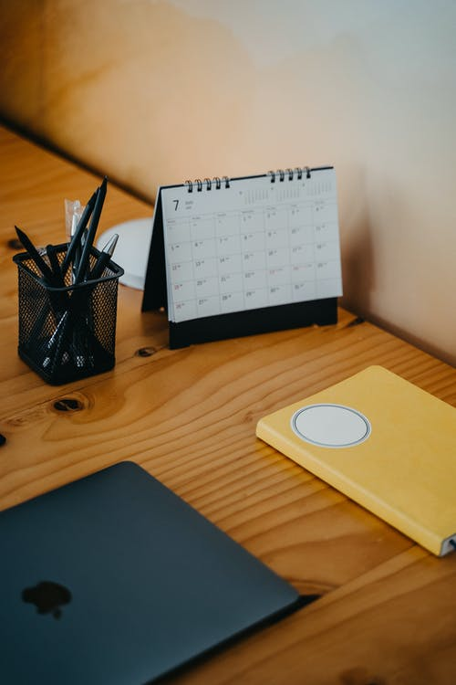 Laptop and Calendar on Wooden Table