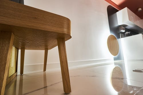 Brown Wooden Table Near White Wall