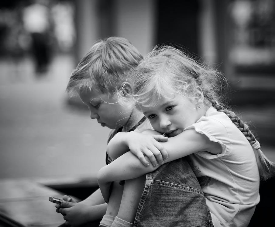 Little sad girl with boy using smartphone